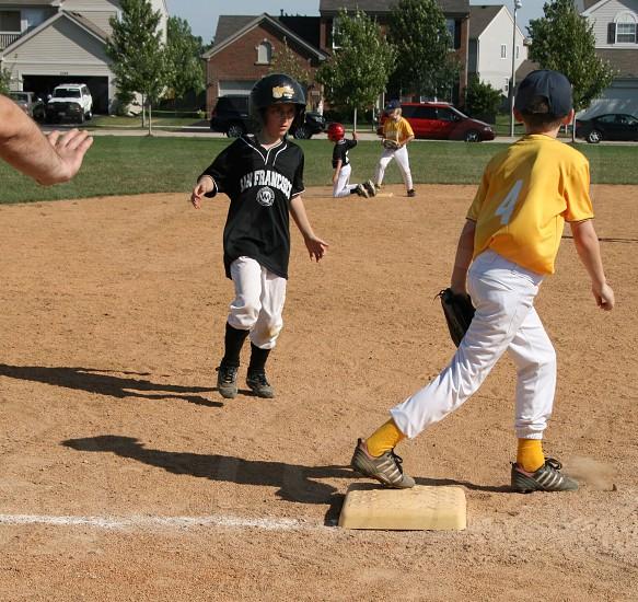boy in black baseball jersey and boy in yellow baseball jersey running photo