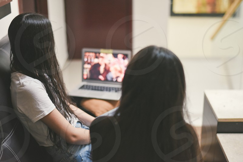 couple of sister watching tv from home photo