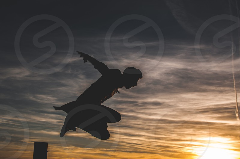 silhouette man jumping at sunset photo
