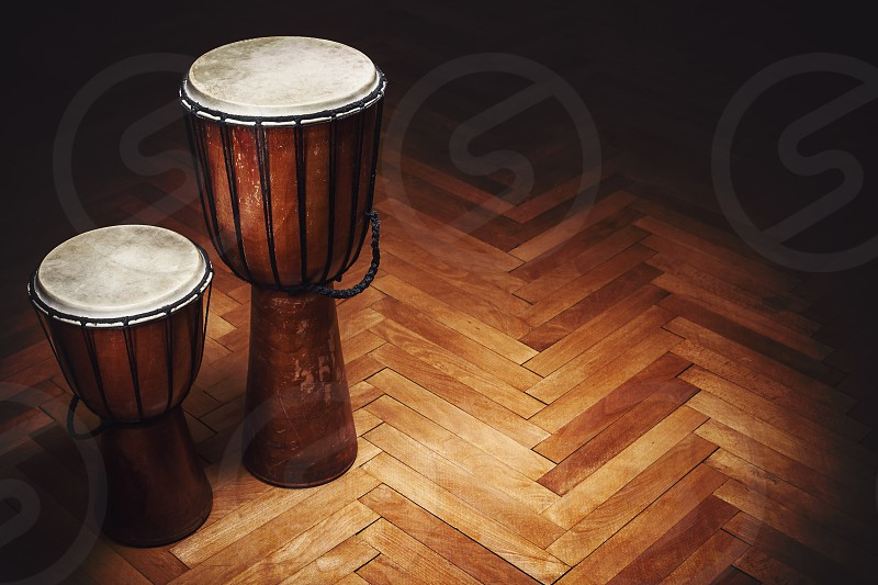 Two old vintage style wooden djembes percussion instruments from Balkan and Africa.  photo