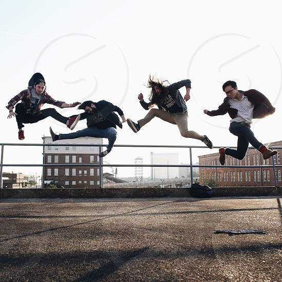 people jumping next to metal hand rails photo