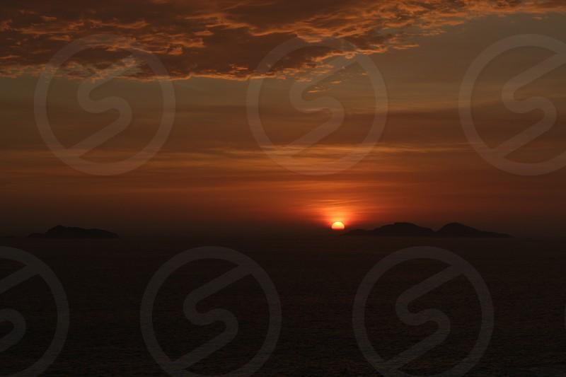 sunset ocean sun sea clouds colors island  photo