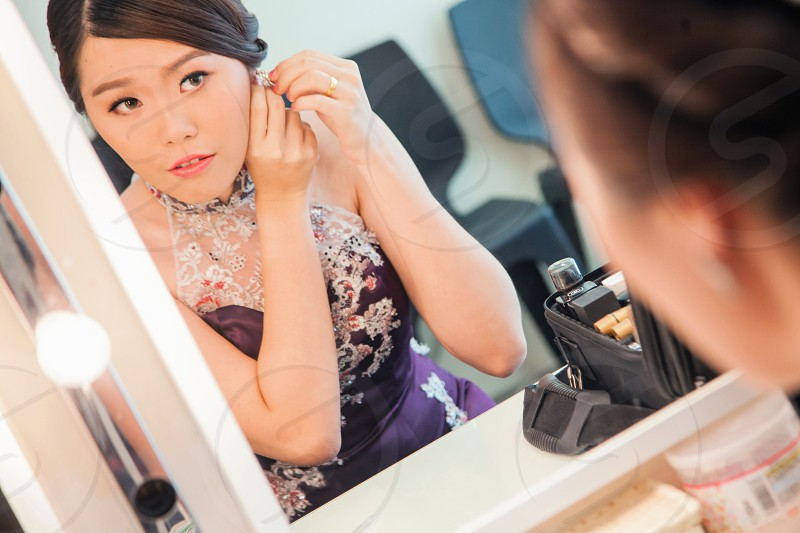 closeup photography of woman in purple halter neck while holding earring front on vanity dresser photo