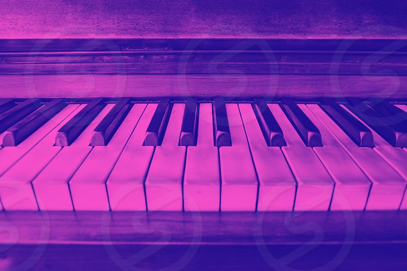 close-up view of the keys of a ancient ruined piano. Purple duotone effect photo
