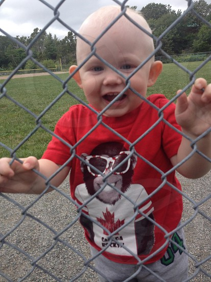 The litte boy smiling at the camera from behind the fence at the ballpark. photo