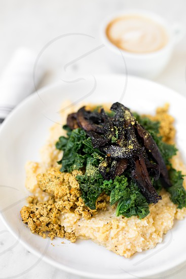 "Vegan grits bowl with tofu scramble kale and portobello ""bacon."" photo"