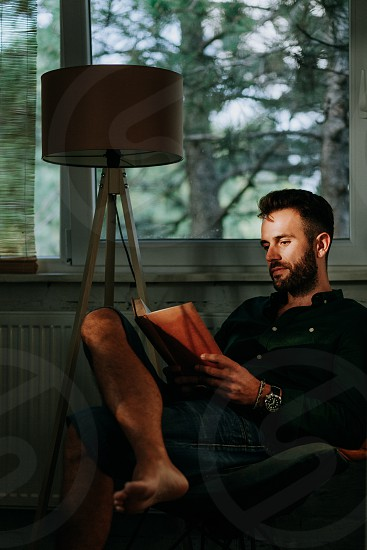 Man reading book at home by the window photo