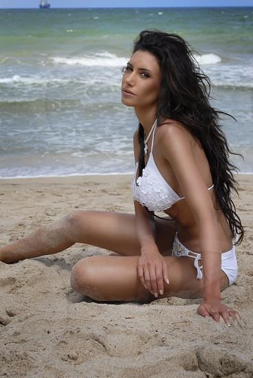 beautiful woman looking at the camera in a white bikini on a tropical beach photo