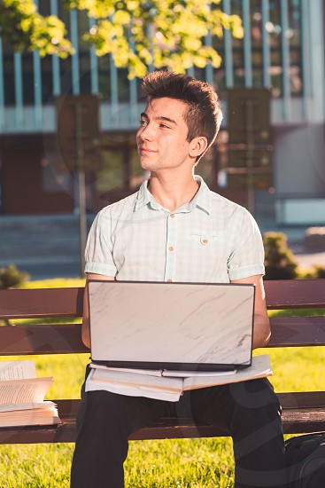 Student working on a laptop using books and notes sitting on a bench in a park. Young boy wearing a blue shirt and dark jeans photo