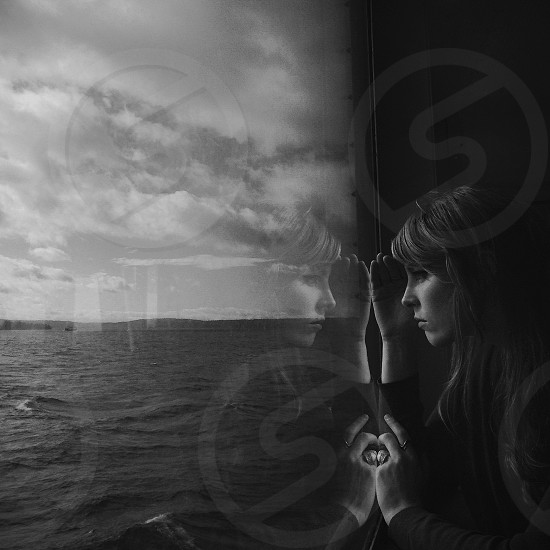 woman facing ocean through glass window in grayscale photography photo