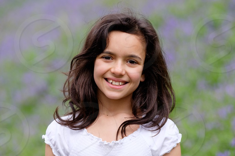 Portrait of a young pretty long dark haired ten year old girl wearing a white top with purple   flowers out of focus behind her photo