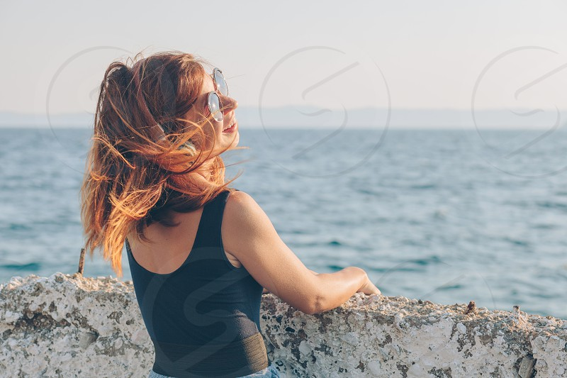Young woman listening to the music on headphones by the sea photo
