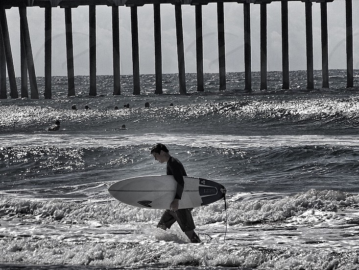 grayscale photo of man carrying surfboard during daytime photo