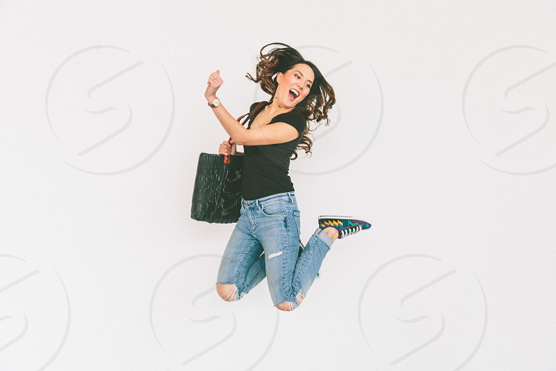 A young woman jumping high into the air against a white wall.  photo