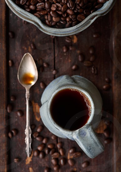 Fresh coffee with beans in a blue earthenware cup photo