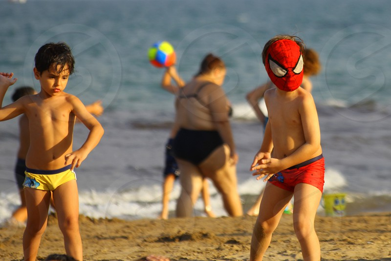 boy wearing spider-man mas standing at the shore together with boy wearing yellow brief during daytime photo