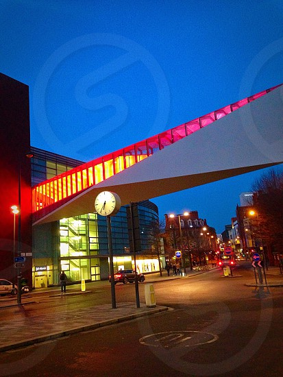city street with lights and a light clock post by a glass building with a enclosed walkover bridge under a blue evening sky photo