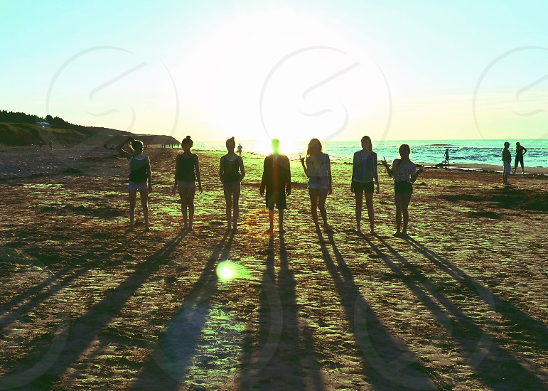 7 people standing on the beach with the sun behind them and their shadows in front of them photo