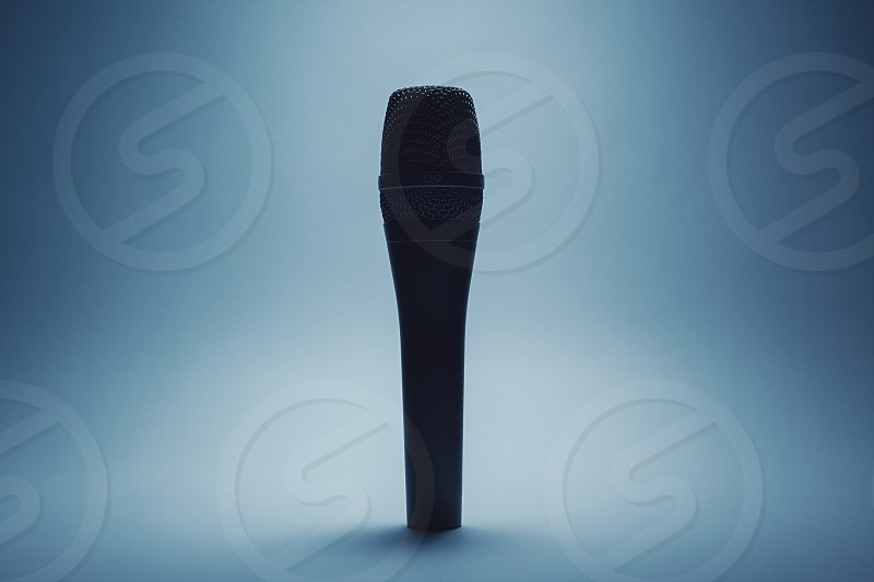 Closeup view of a modern microphone highlighted parts by illumination. photo