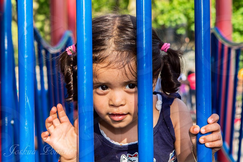 girl looking at through blue metal bars photo
