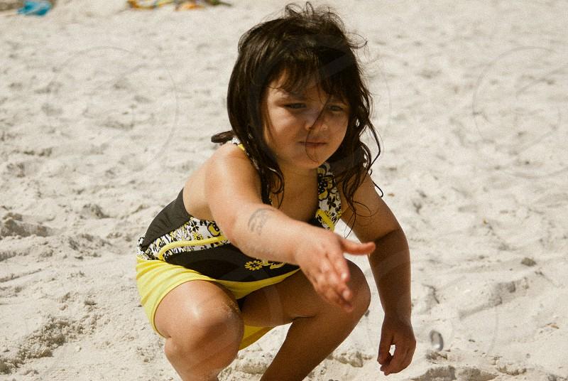 girl crouching on sand photo