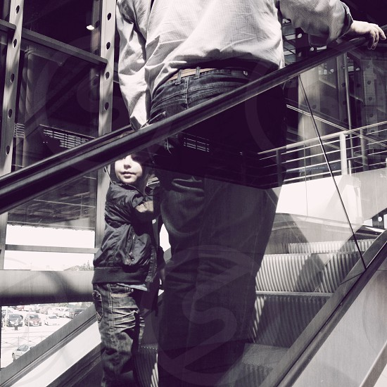 man and child on escalator going up photo