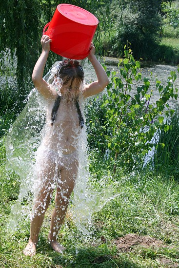 nude girl pouring a bucket of water to herself photo