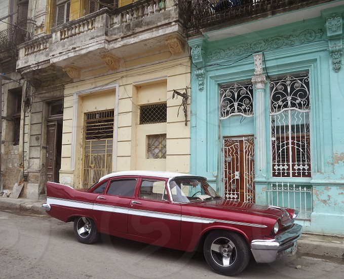 Vintage car parked in front of peeling historic buildings Havana Cuba photo