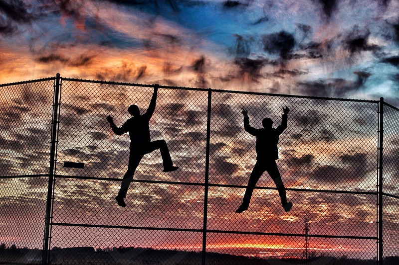 human climbing in the fence silhouette  photo