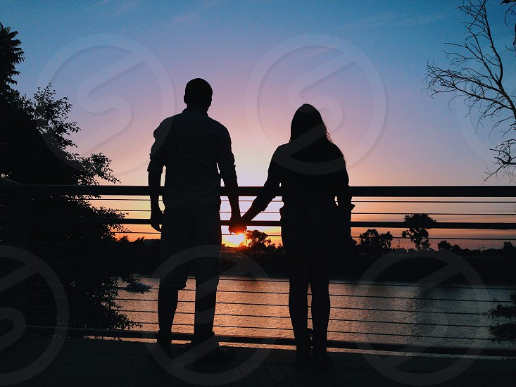 man and woman standing under sunset photo
