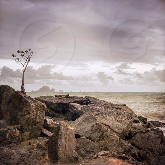 Outdoor day colour square filter Krabi Ao Nang Thailand Thai Kingdom Beach sea ocean shore waves Asia Asian view vista sky clouds summer rocks rocky travel tourism wanderlust tourist water splash spray wet limestone cliffs tree Nature foliage crack crevices rugged bay cloudy atmospheric stormy photo