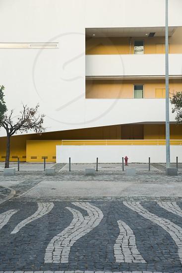 building architecture Lisbon Portugal yellow white cobblestone lines street travel photo