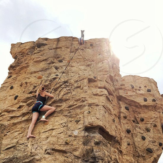 woman in black tank top climbing on sheer rock wall holding on to safety line anchored on top photo