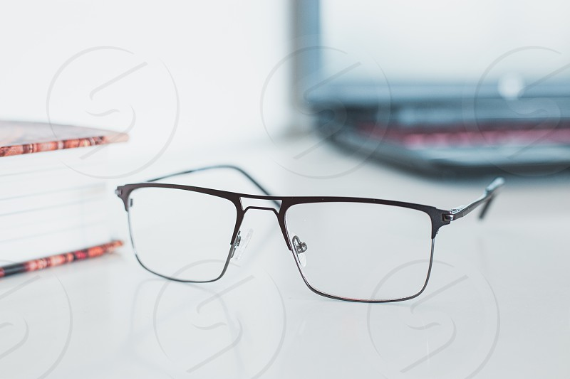 Glasses with book and laptop photo