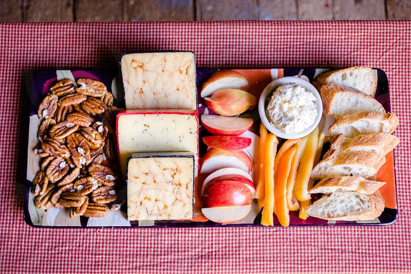 brown nuts slices of cheese apple slices yellow fruit slices and baguette slices aligned on white and blue rectangular platter on white and red gingham textile photo