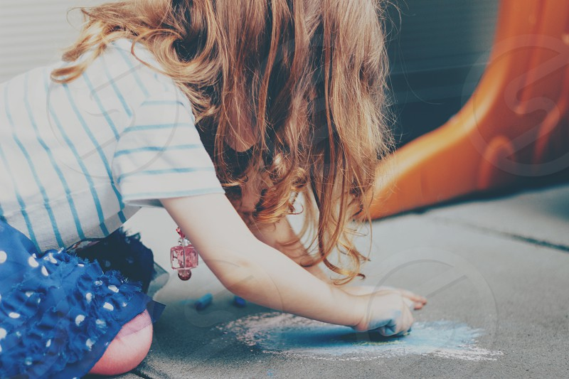 Young girl coloring chalk outside playing creative photo