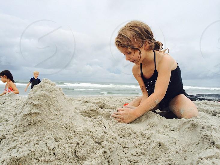 girl in black leotard on beach sand photo