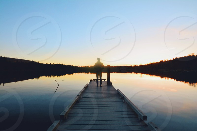 person standing on brown wooden dock on lake during sunset photo