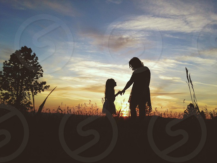 person holding hand of little girl in front of sunset photo