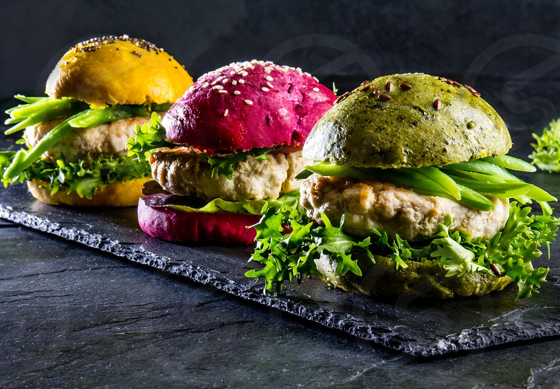 Colored green yellow and purple burgers on slate board. Close up photo