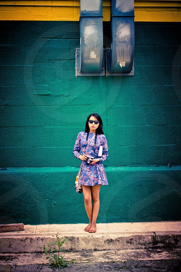 woman wearing blue and pink floral print mini dress standing under two blue vents photo