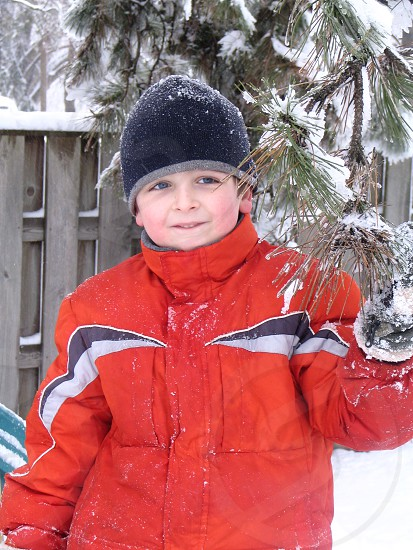 snow day! smiling boy with snow on coat and hat by snowy pine photo