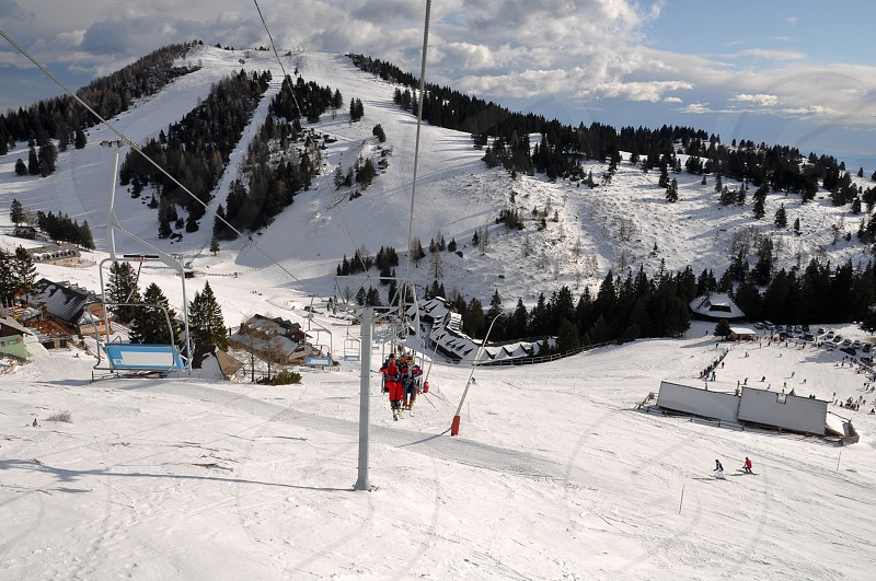 Ski slopes of Alpine wintersport resort Krvavec in Slovenia people skiing and riding a skilift into the valley photo