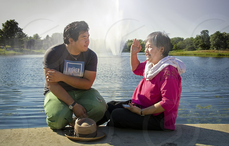 Authentic Family life in China Chinese mother and son sitting talking by a lake with fountain in the bright sunlight on a sunny summer day photo