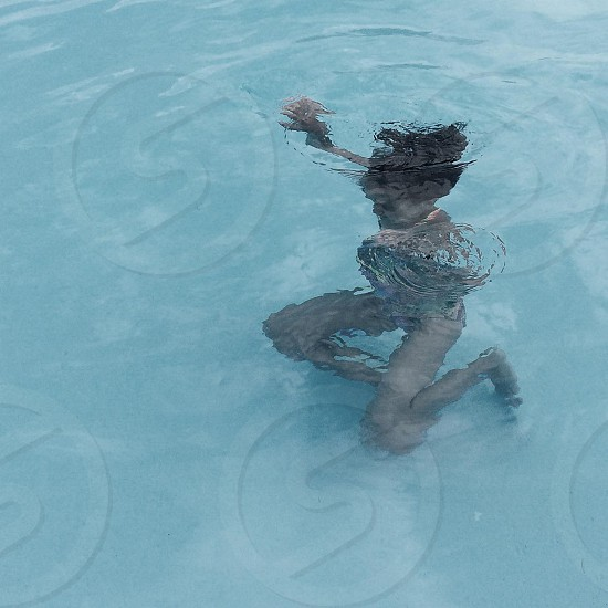Girl in a pool of blue water with her reflection skewed photo