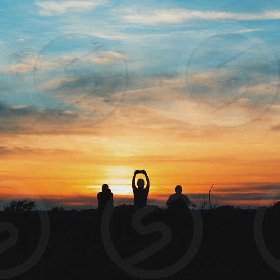 silhouette of 3 person during sunset photo
