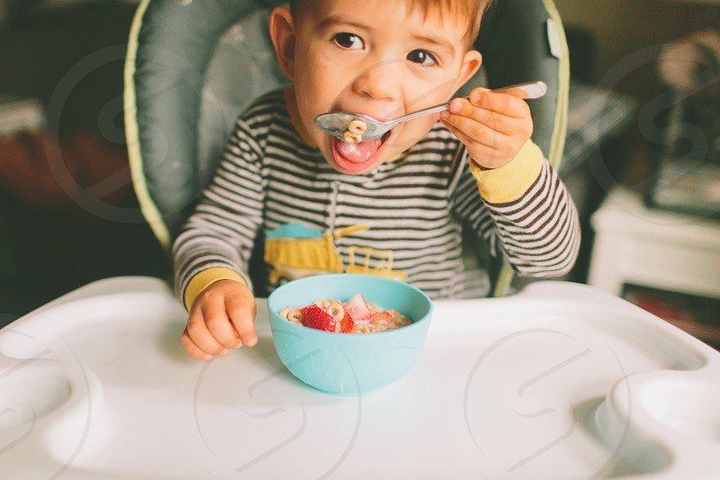 A little boy eating cereal for breakfast in his high chair.  photo
