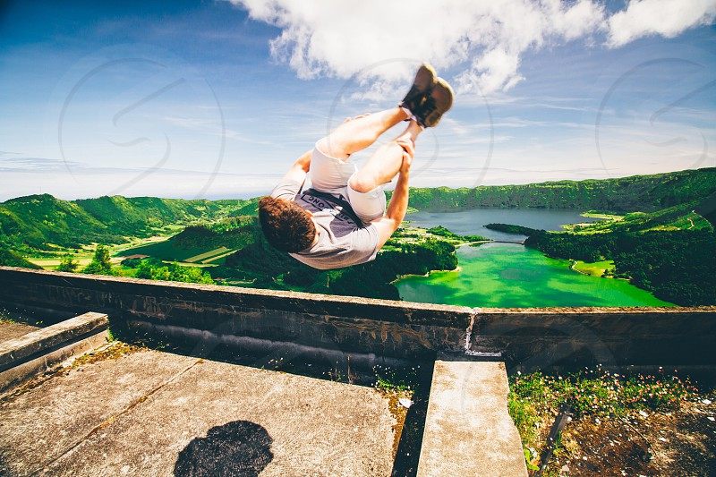 man in grey shirt doing back flip under blue sky with white clouds during daytime photo