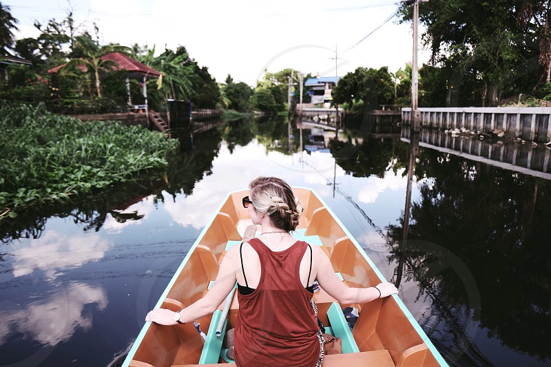 woman in red tank top riding brown boat on body of water at daytime photo