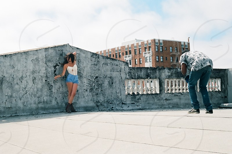 man in blue daisy dukes standing beside gray concrete wall photo